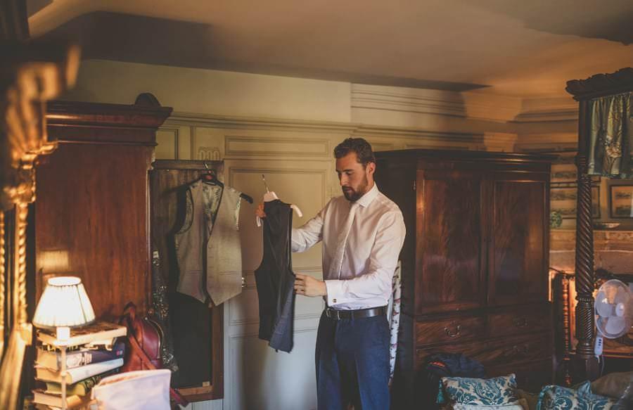 The groom picks up his waistcoat in his bedroom