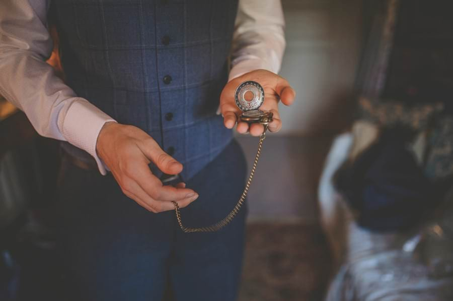 The groom holds his grandfathers watch in his left hand