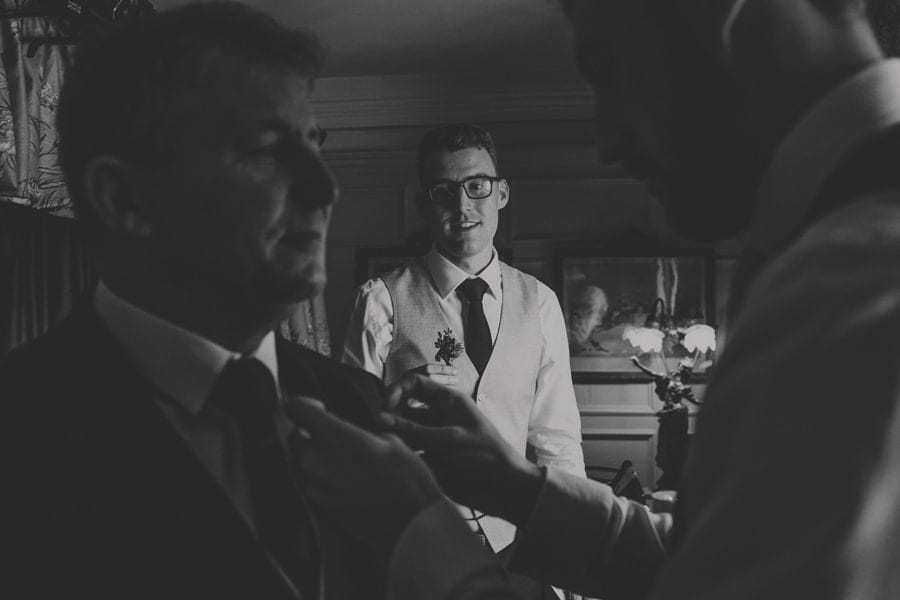 The grooms brother watches as the groom fixes a flower on the lapel of his fathers suit