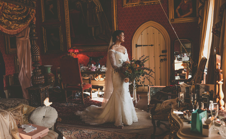 The bride looks out of the window as she holds her flowers in the bridal suite at Maunsel house
