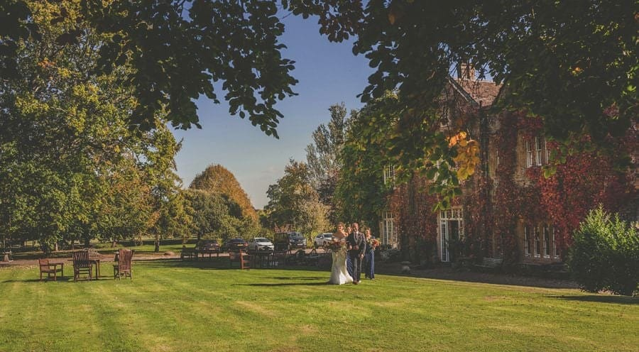 The bride, her father and the bridesmaids walk across the lawn at Maunsel house towards the outdoor ceremony