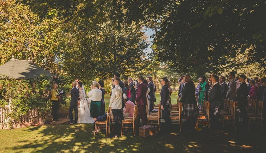 The bride, groom and wedding guests stand under the tress of the outdoor wedding ceremony at Maunsel house