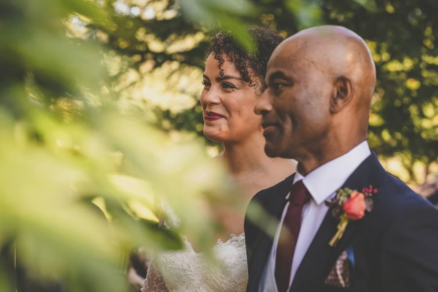 The bride stands next to her father and smiles during the outdoor ceremony