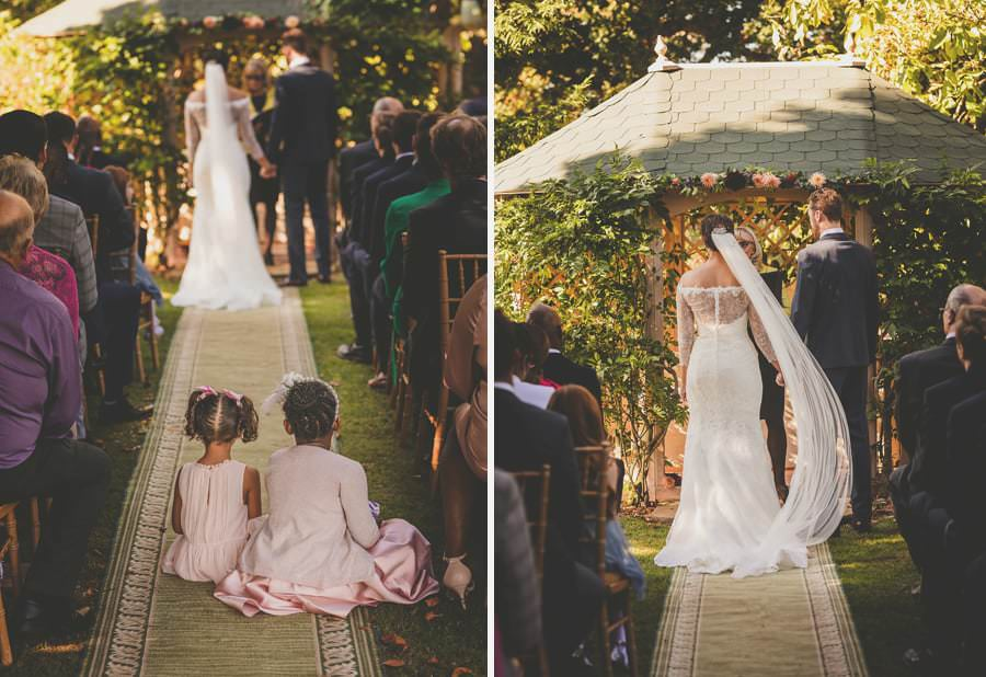 Flowergirls sit in the aisle of the outdoor ceremony on the lawn at Maunsel house