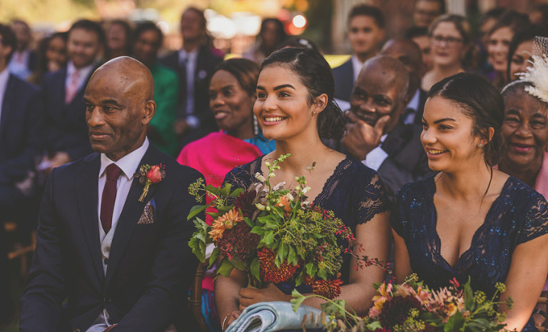 A bridesmaid smiles as she sits next to her family in the outdoor wedding ceremony