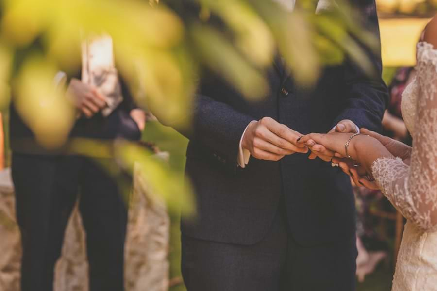 The groom places the wedding ring on the brides finger