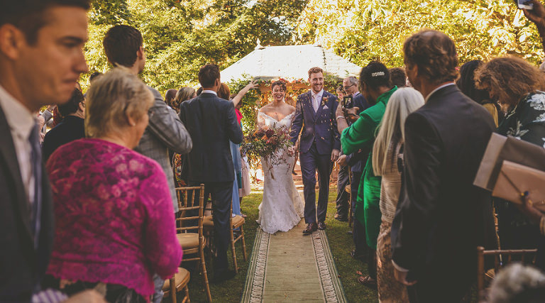 The bride and groom walk down the aisle together at the end of the outdoor ceremony at Maunsel House