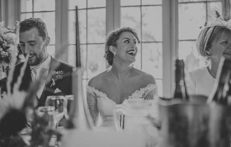 The bride laughs as her father delivers his wedding speech
