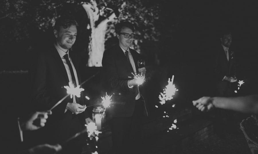 Wedding guests light sparklers in the evening at the back of Maunsel House