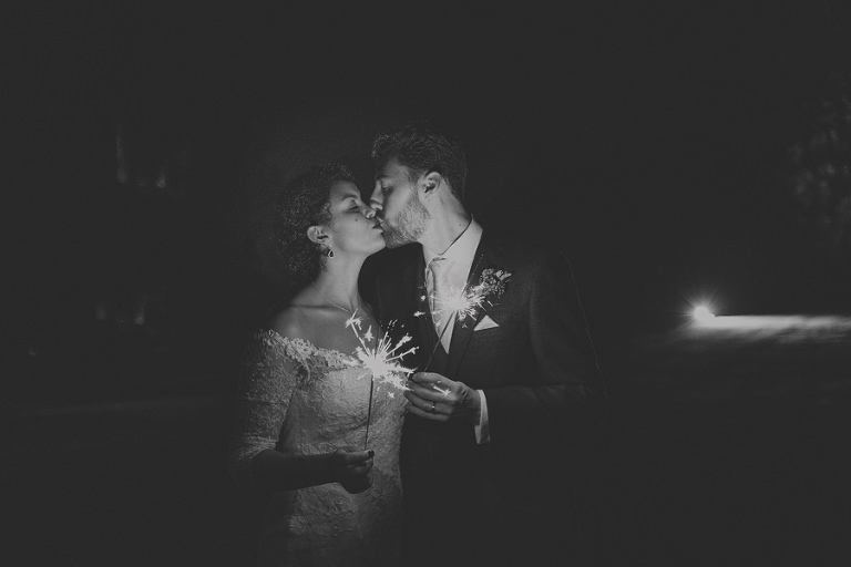 The bride and groom hold sparklers and kiss each other