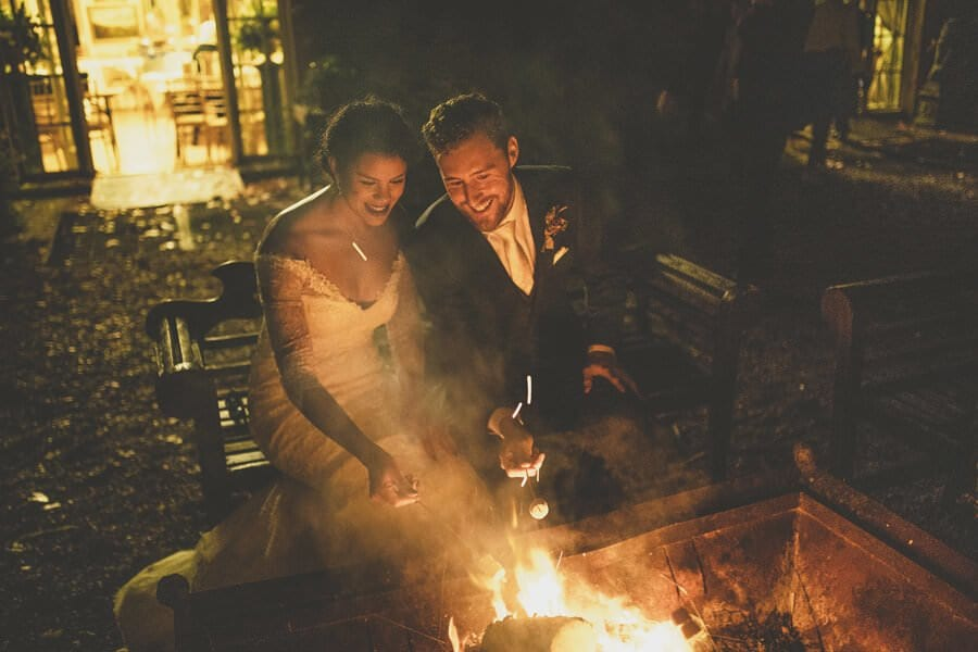 The bride and groom toast marshmallows in front of an open fire outside Maunsel House