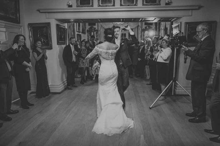 The bride and groom hold hands and dance in front of their wedding guests at Maunsel House