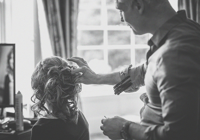 The hairdresser ties the back of the bridesmaids hair as she looks into the mirror