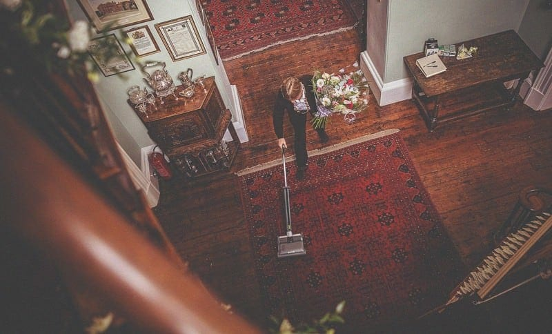 A lady holds flowers in one hand and holds a vacuum cleaner in her other hand in the hallway at homme house