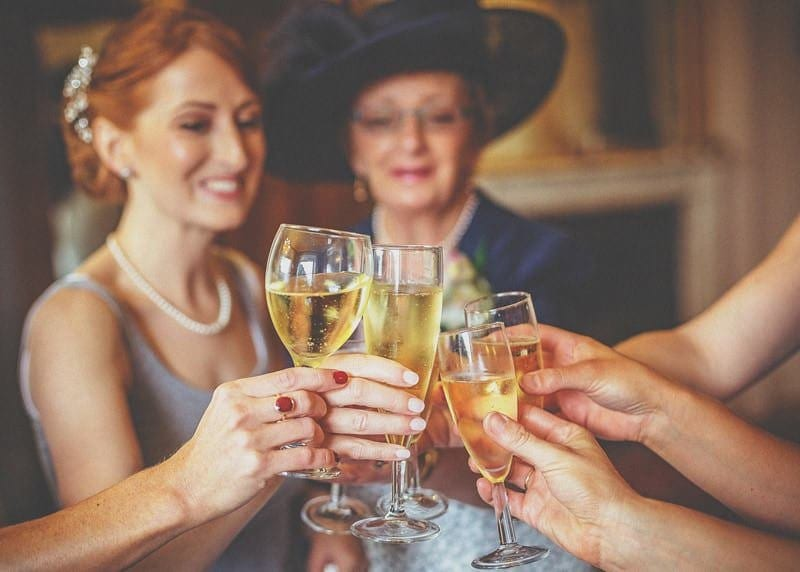 The bride and her bridesmaids place their champagne together and make a toast