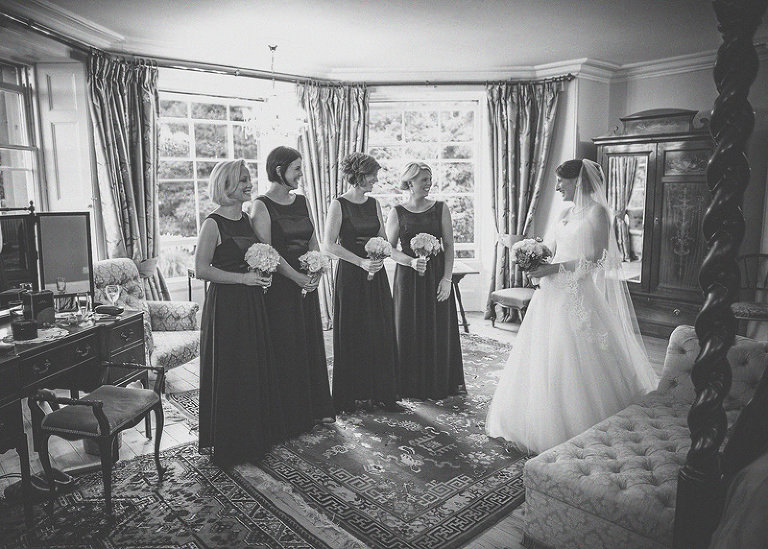 The bride and her bridesmaids stand together all holding their flowers
