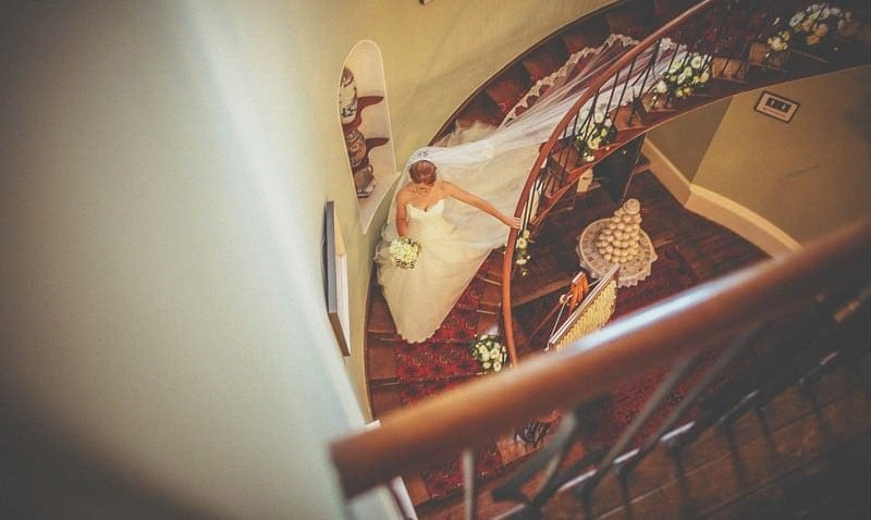 The bride walks down the spiral staircase in homme house