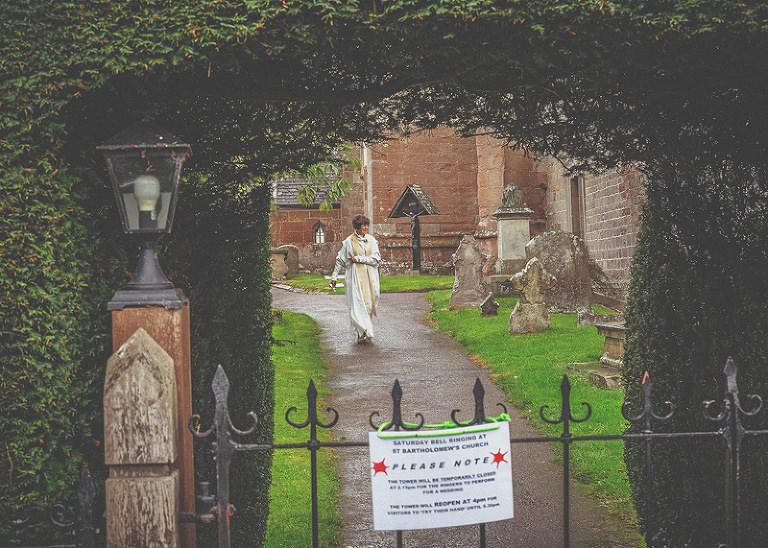 The vicar at st.bartholomes church walks down the path