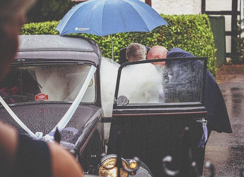 The bride is helped out of the vintage car outside St Bartholomes church