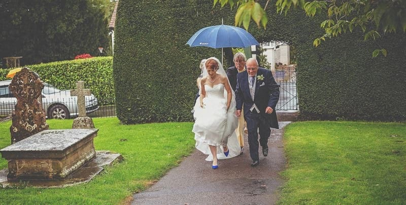 The bride, her father and her bridesmaids walk up the path of St Bartholomews church in the rain