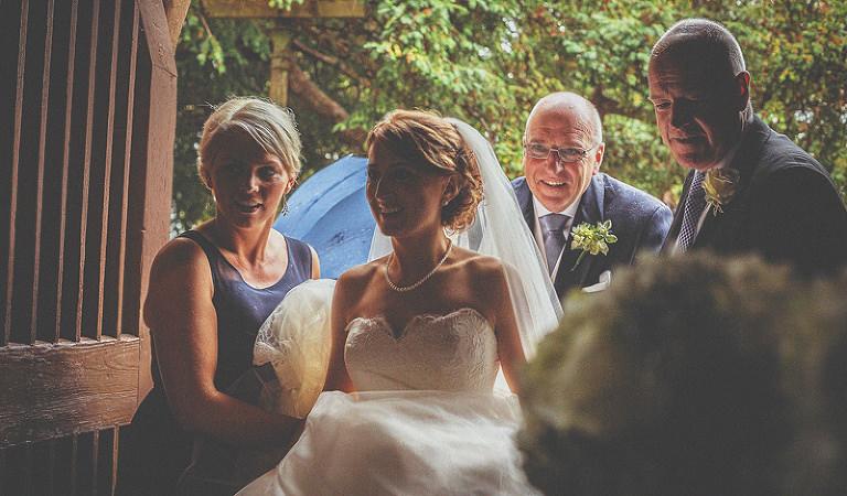 The bride, her father and the bridesmaids arrive at the door of St Bartholomes church