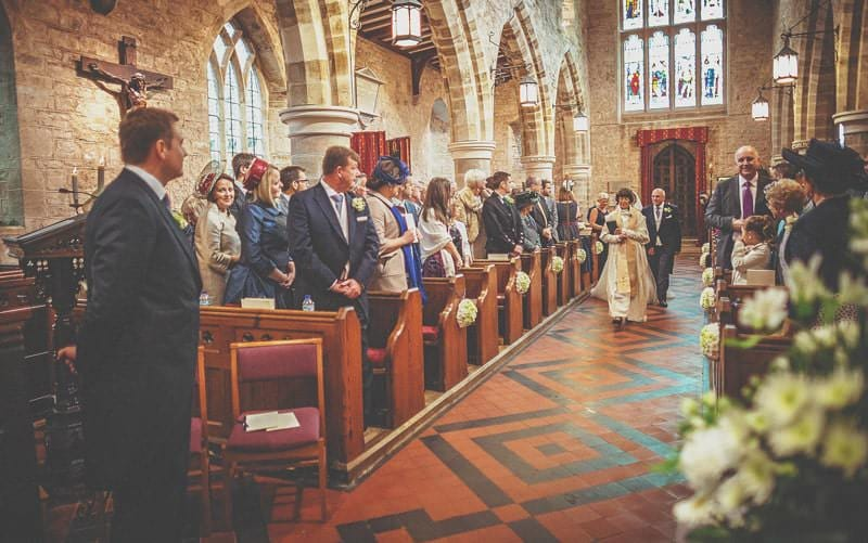 The vicar, the bride and her father walk up the aisle at St Bartholomes church