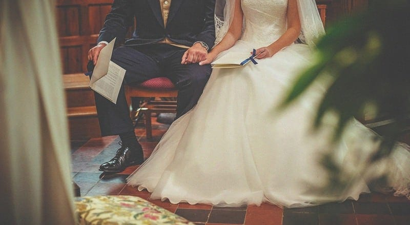 The bride and groom sat down holding hands in church during the wedding ceremony