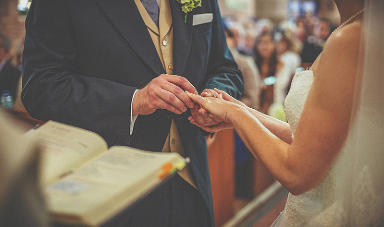 The groom places the ring on the finger of the bride during the wedding ceremony in St Bartholomews church