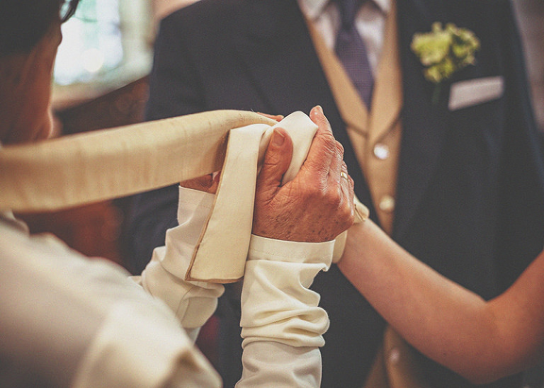 The vicar places his robe around the bride and grooms hands during the wedding ceremony