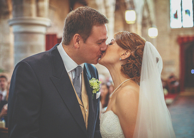 The bride and groom share a kiss in church during the wedding ceremony