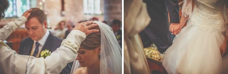 The vicar places his hands on the heads of the bride and groom