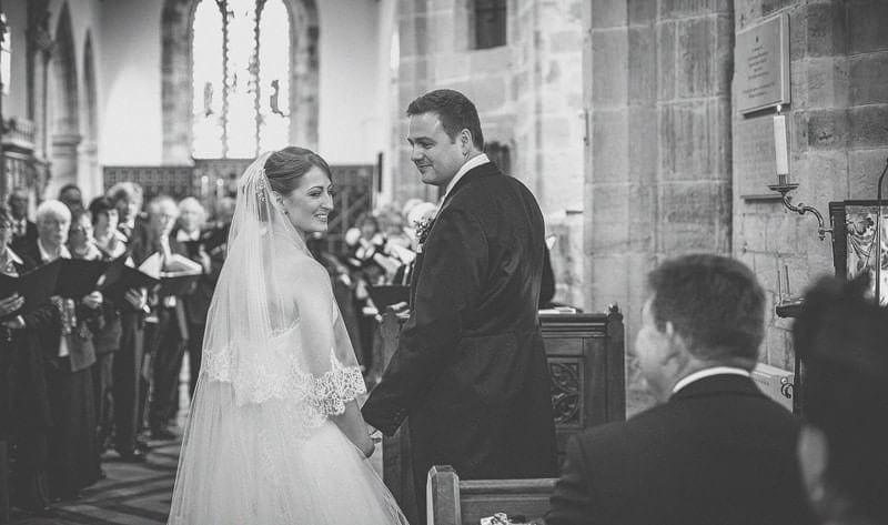 The bride and groom turn around during the wedding ceremony and smile at friends and family