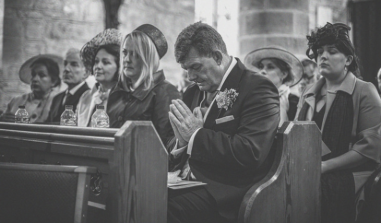 The best man sits in church and prays during the wedding ceremony
