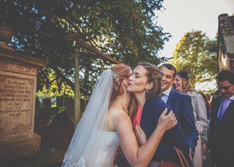 A wedding guest kisses the bride in the gardens of St Bartholomews church