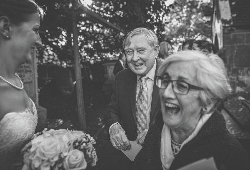 A wedding guest and his wife laugh together with the bride in the gardens of St Bartholomews church