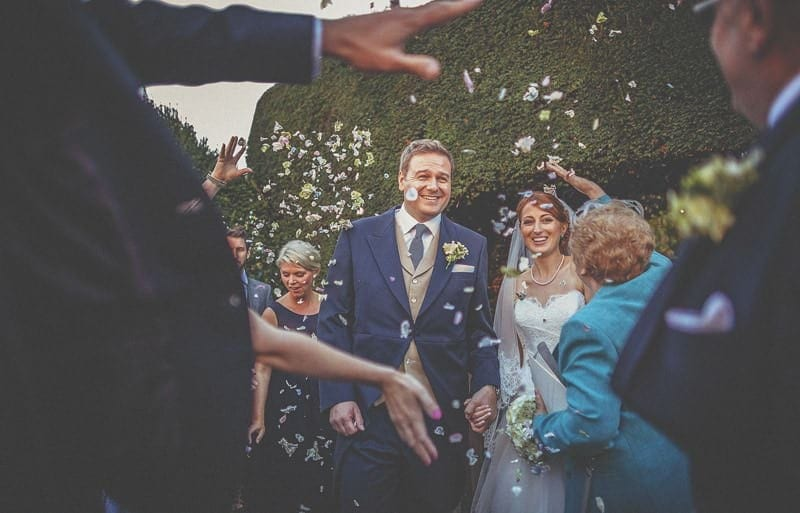 The bride and groom are showered in confetti in the gardens of St Bartholomews church