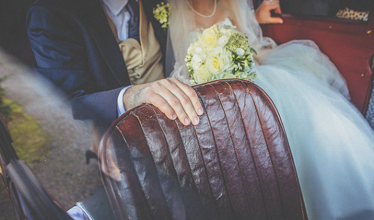 The groom places his hand on the drivers seat as they sit in the back of the vintage car