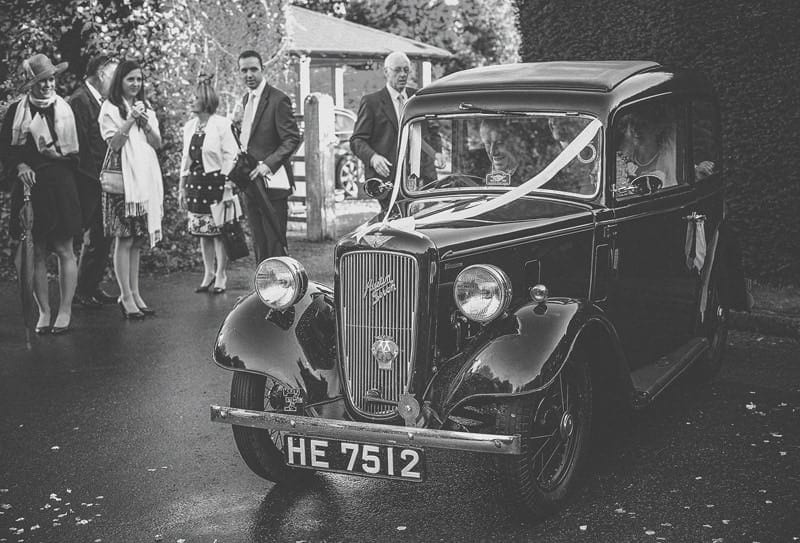 The old vintage car leaves St Bartholomews church with the bride and groom inside the car