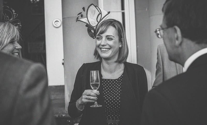 A wedding guest holding a glass of champagne smiles with friends and family