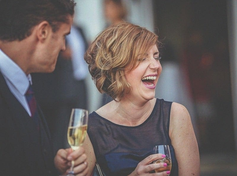 A wedding guest holding a glass of champagne closes her eyes and laughs