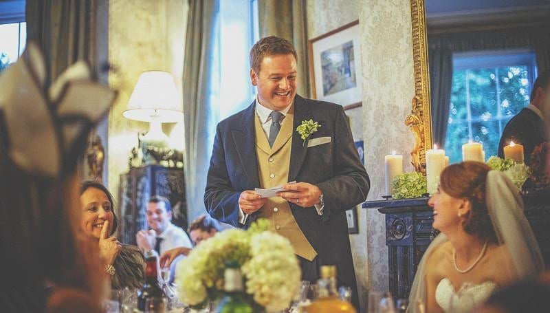 The groom stands up and delivers his speech to the wedding party at homme house