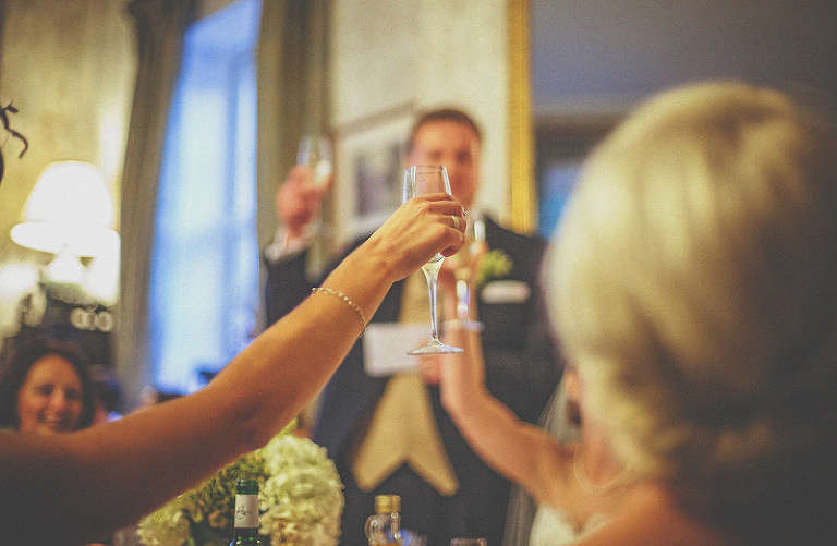 A lady raises a glass of champagne at the end of the best mans speech