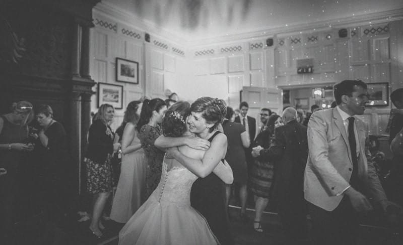 A bridesmaid embraces the bride on the dancefloor at homme house