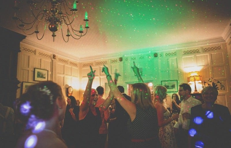 The bridesmaids raise their arms in the air during a song they are dancing to at homme house