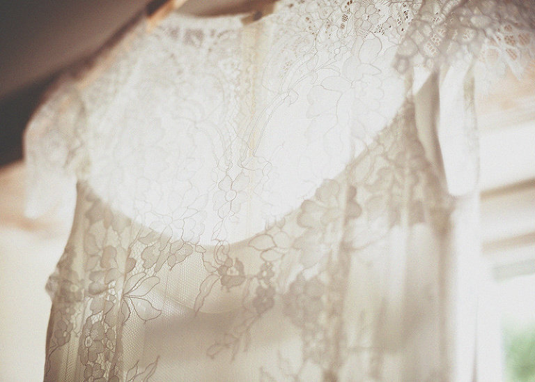 The brides dress hangs next to a window