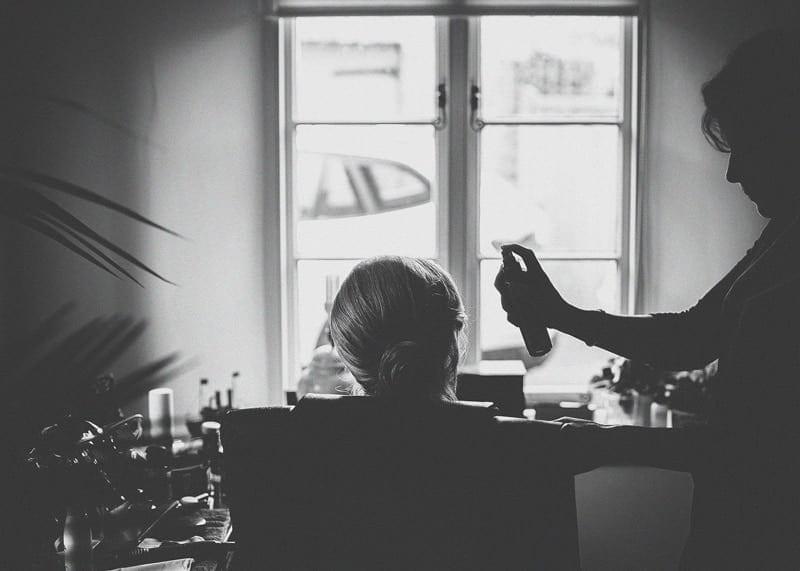 The hairdresser sprays a bridesmaids hair