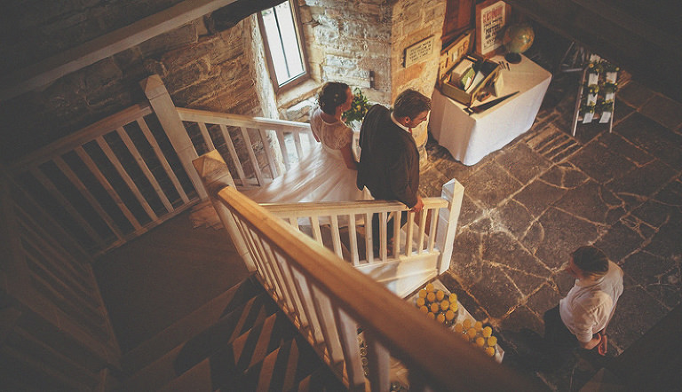 The bride and groom walk down the staircase of the barn