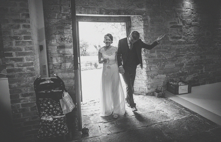 The bride and groom walk into the barn