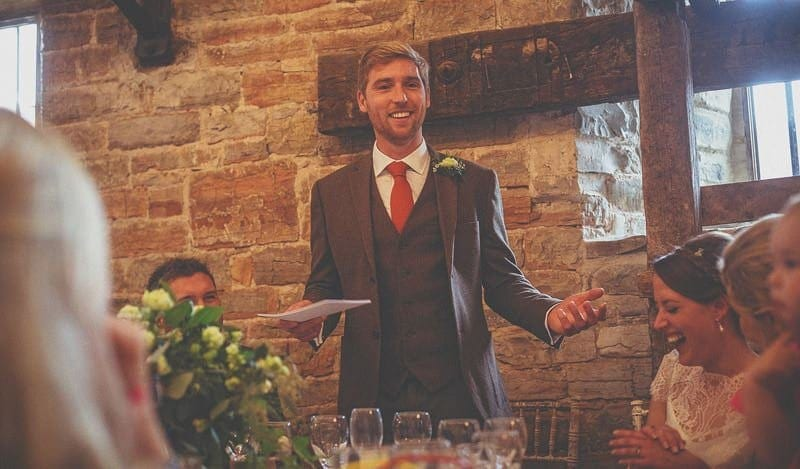 The groom stands up and smiles as he delivers his speech to the wedding party