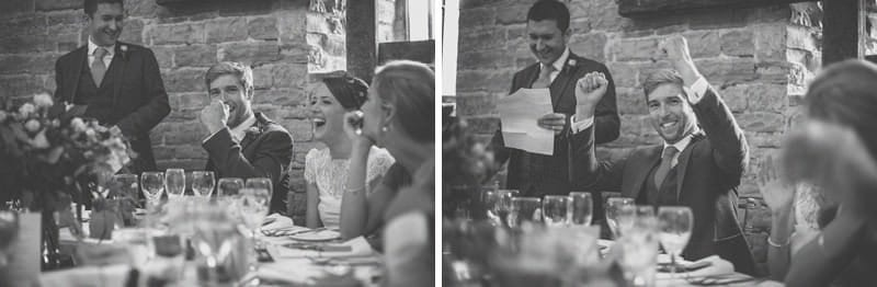 The groom laughs and raises his arms in the air during a wedding speech